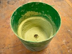 Creating a concrete planter using a 5 gallon plastic bucket ... Pack handfuls of material up the side walls, about 1/4″ in thickness, adding too much concrete at one time will cause the walls to slump down.  After concrete has cured, pry walls of bucket away from the concrete to break the seal. Turn the bucket over and the weight of the piece should let it drop/slide out ... http://www.concreteexchange.com/how-to-center/small-projects/5-gallon-planter-gfrc/