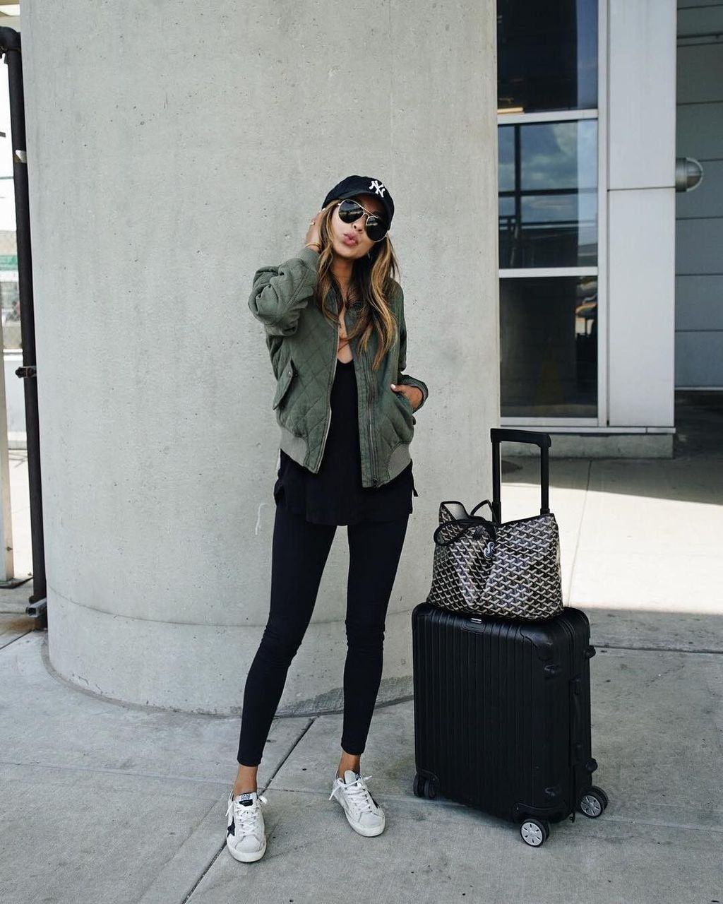 c9756836edd5 Bomber Jacket - The ultimate cool-girl airport outfit  Sincerely Jules   olive green bomber jacket and black legging combo.