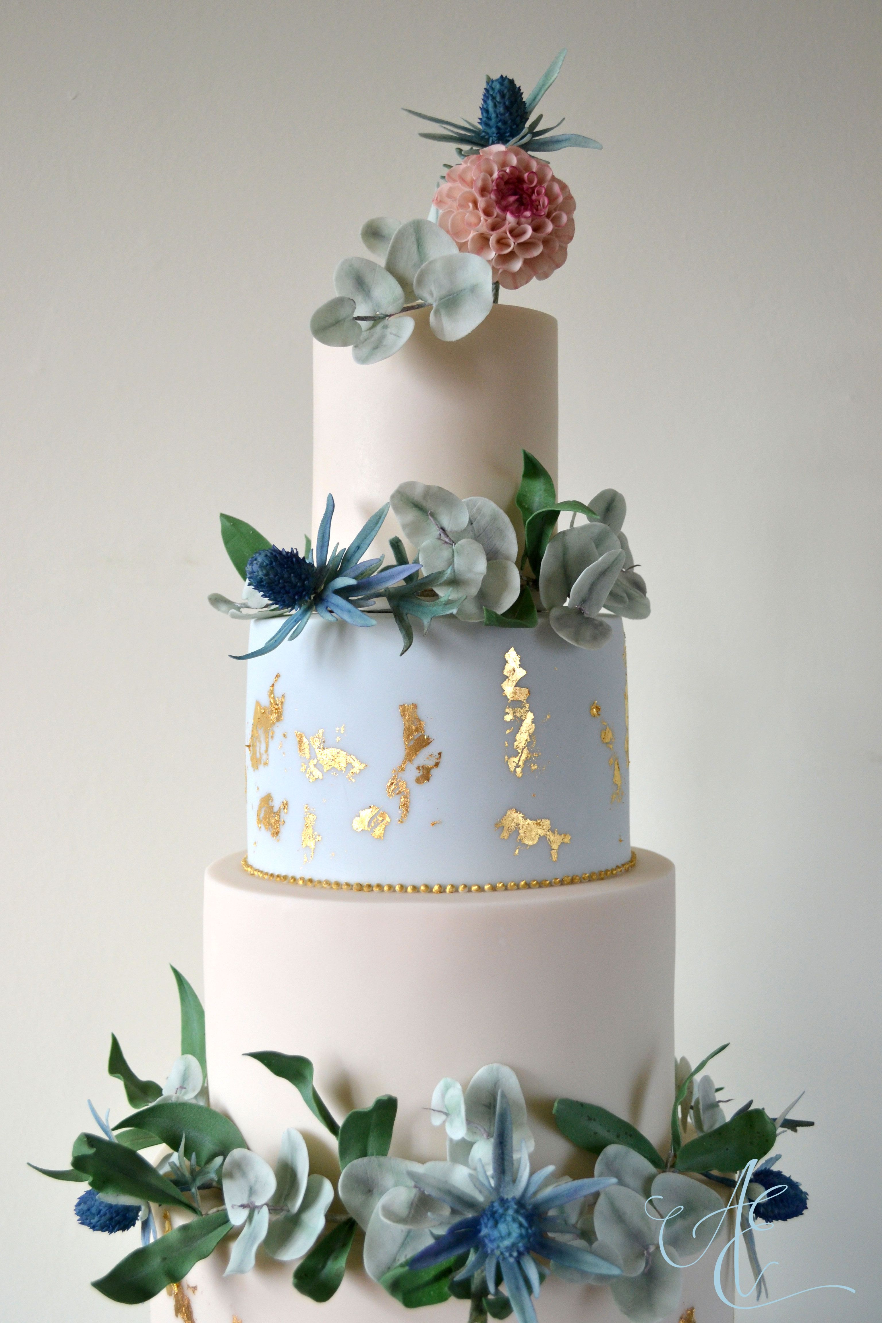 Botanical Meets Opulent Wedding Cake Decorated With Garlands Of Sugar Foliage And Sea Holly A Botanical Wedding Cake Whimsical Wedding Cakes Gold Wedding Cake