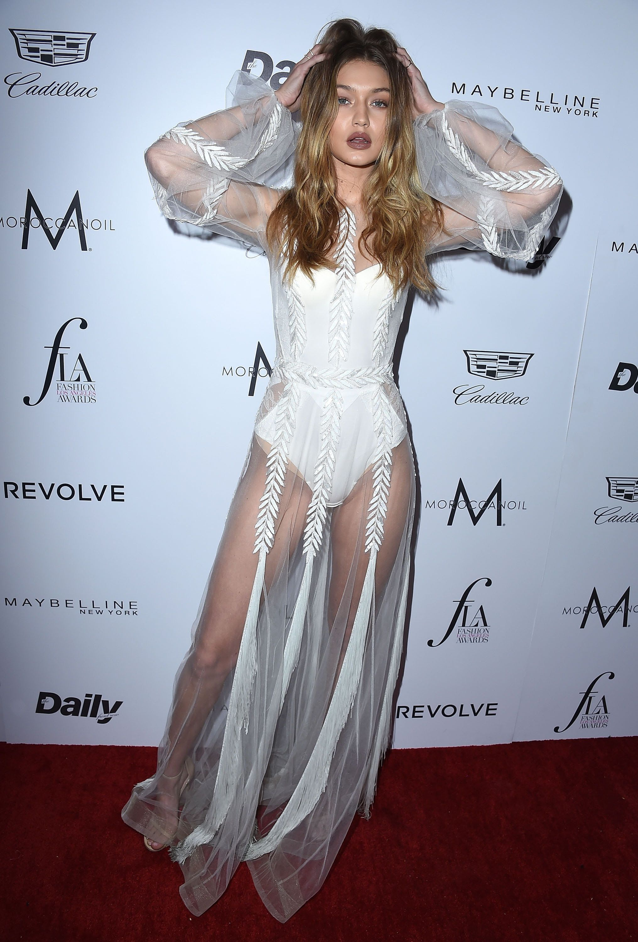 fb3bcc014e84 Gigi Hadid at the 2016 Daily Front Row Awards wearing a white sheer Yanina  Couture dress over a La Perla bodysuit with Stuart Weitzman Nudist Strapy  Heels