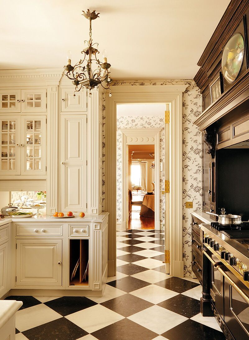 Classically appointed kitchen has a checkerboard marble floor in