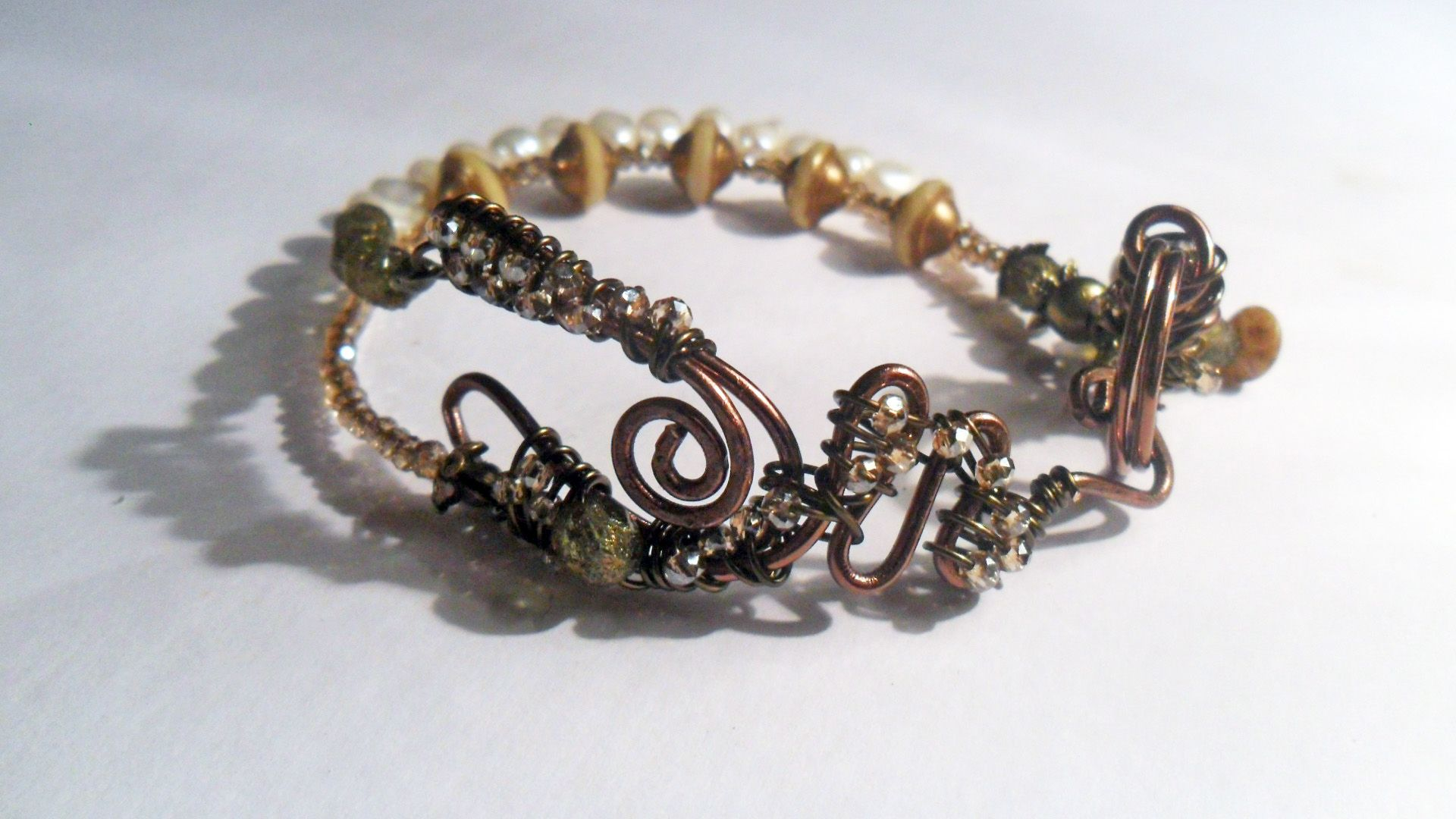 Sold almost instantly, this is a unique handmade bracelet with a wire wrapped clasp, emblazoned with tiny old gold tone faceted Swarovski crystals. The dual strands of the bracelet itself are filled with more of the same crystals, freshwater pearls, and handmade lamp work ivory and gold beads. Beautiful even if I do say so myself!