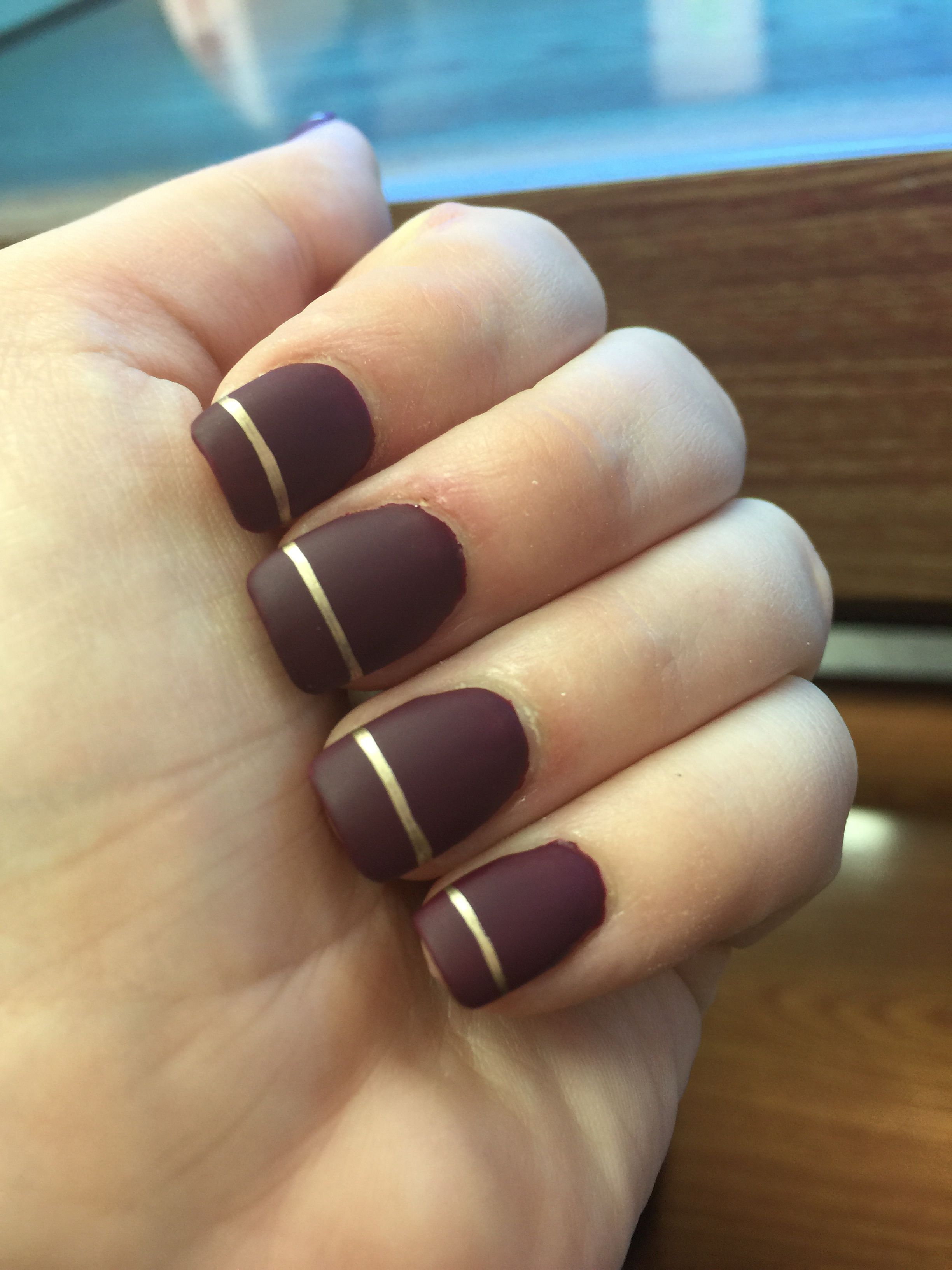 Matte burgundy nails with metallic gold line - by Katherine