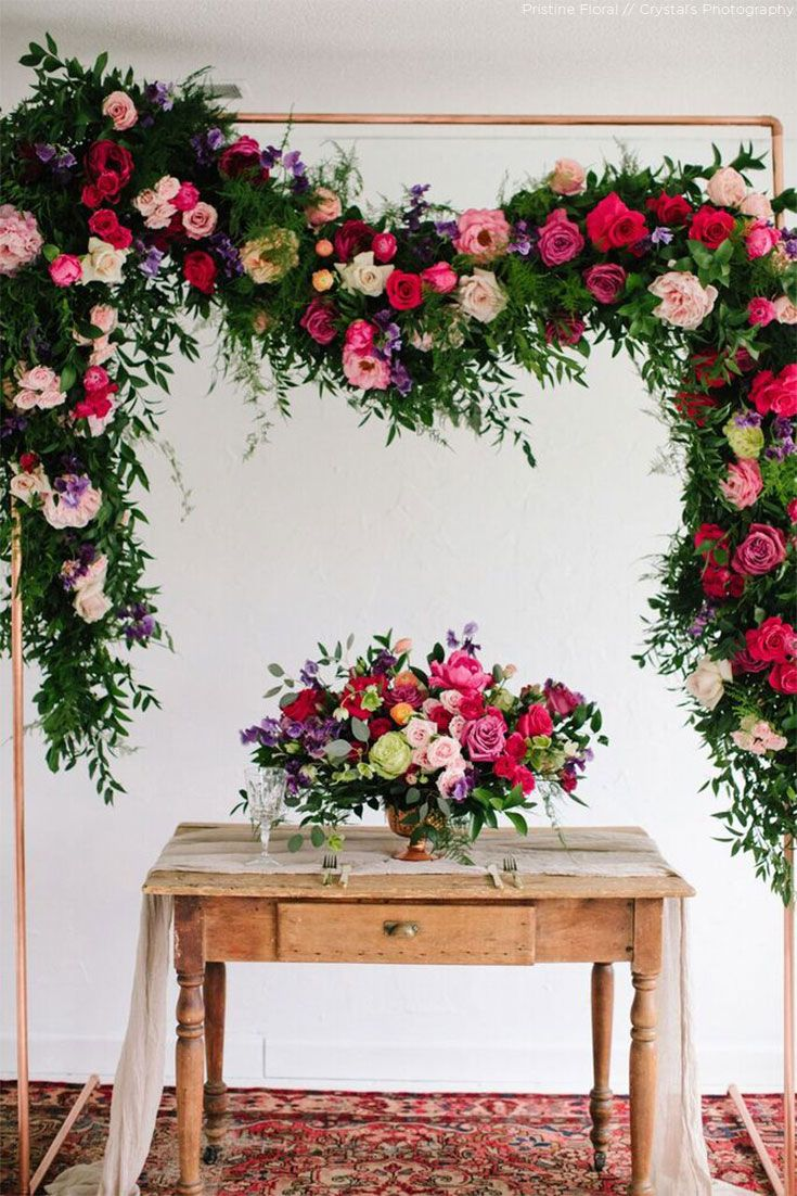 Flourishing silk flower backdrop with a gorgeous centerpiece to ...