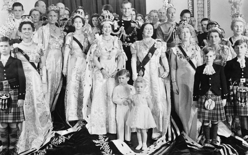 4 June 1953: A smiling Queen Elizabeth II poses with her family and members of the Royal family in the throne room at Buckingham Palace, after her coronation. In front are the Queen's two children, Prince Charles and Princess Anne, while behind her is her husband, the Duke of Edinburgh. At her right is her sister Princess Margaret, while at her left is the Queen Mother.