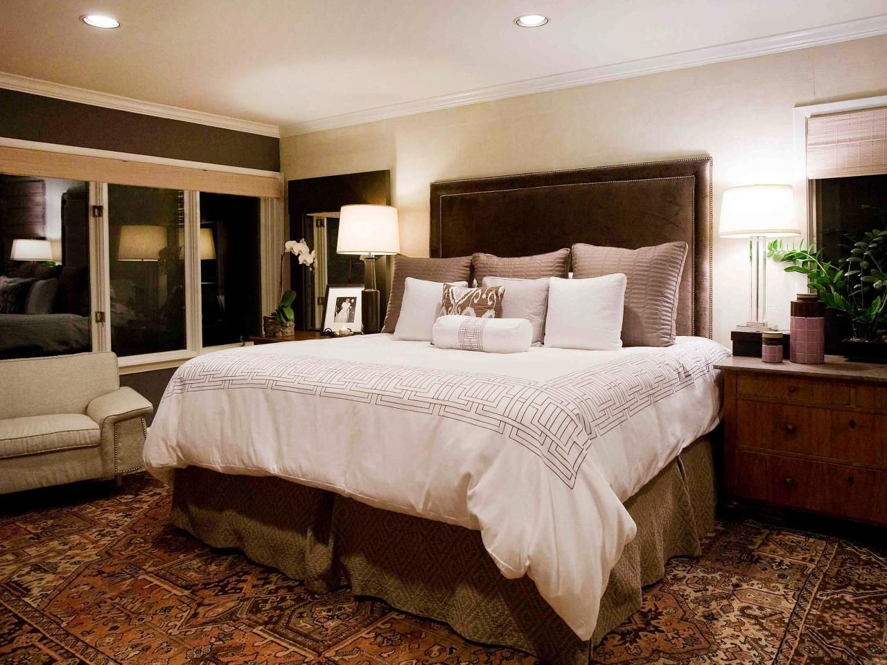 This master bedroom has neutral walls and an upholstered brown