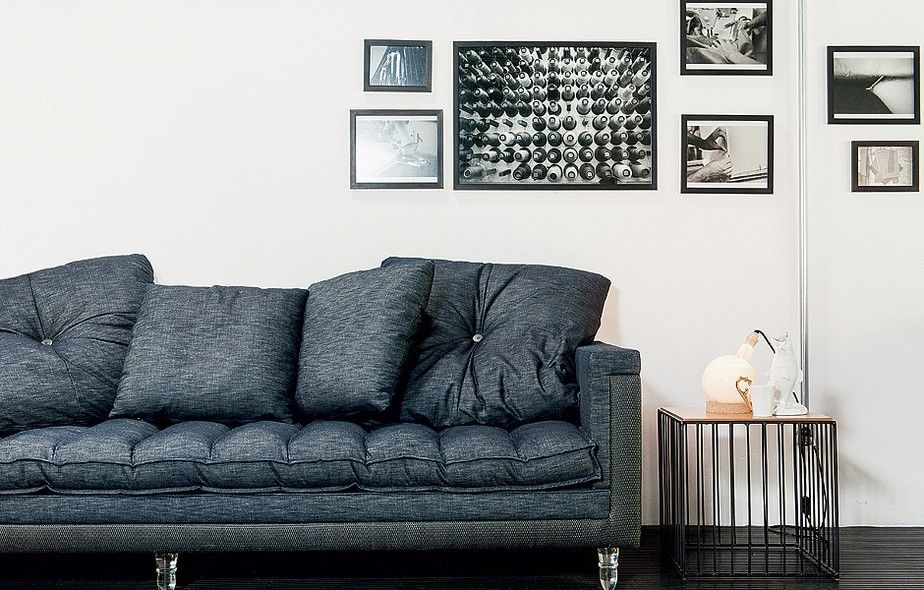 Com finas grades, essa mesa lateral causa um belo efeito na sala. Os tons de preto e cinza deste ambiente recebem o contraste das paredes brancas, deixando o visual clean e moderno