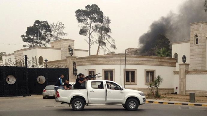 Forces loyal to rogue general storm Libya's parliament, demand suspension: Armed men aim their weapons from a vehicle as smoke rises in the background near the General National Congress in Tripoli May 18, 2014. (Reuters)