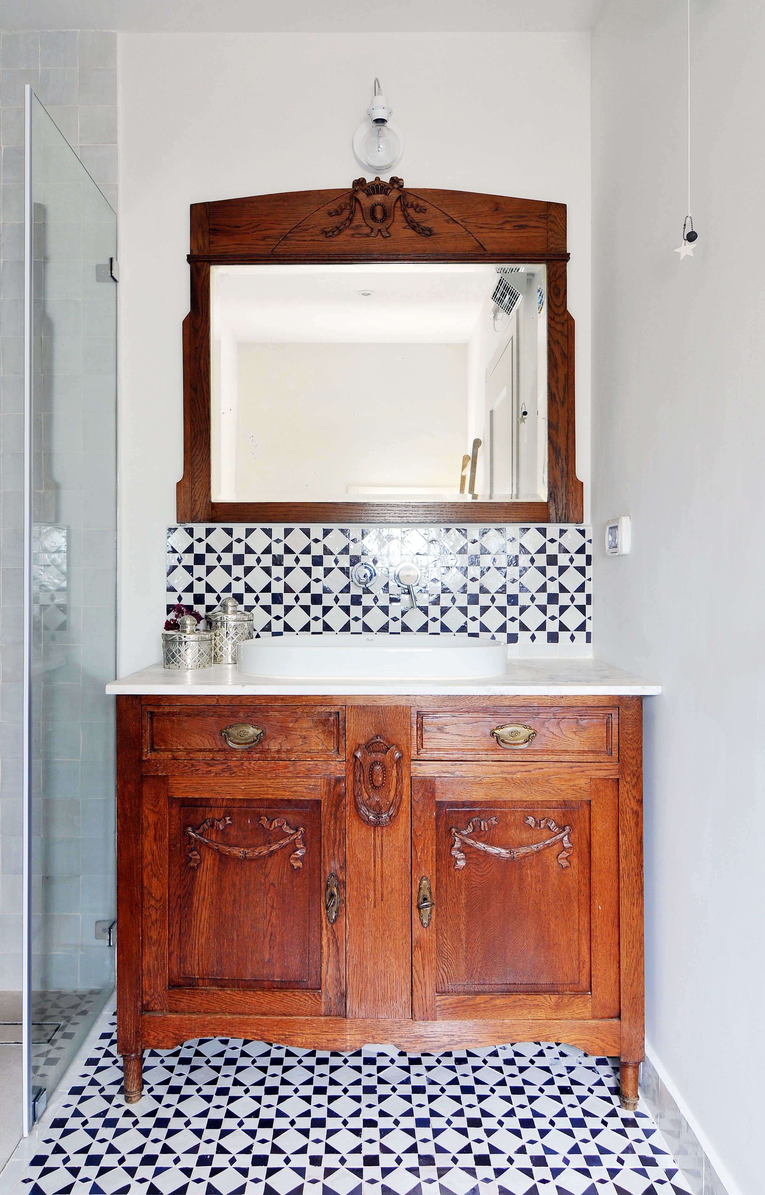 A wooden cabinet in a black and white bathroom. Designed by Liat Hadas, Architecture & Design.