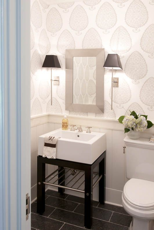bathroom with a lovely wallpaper, wall sconces e a simple but