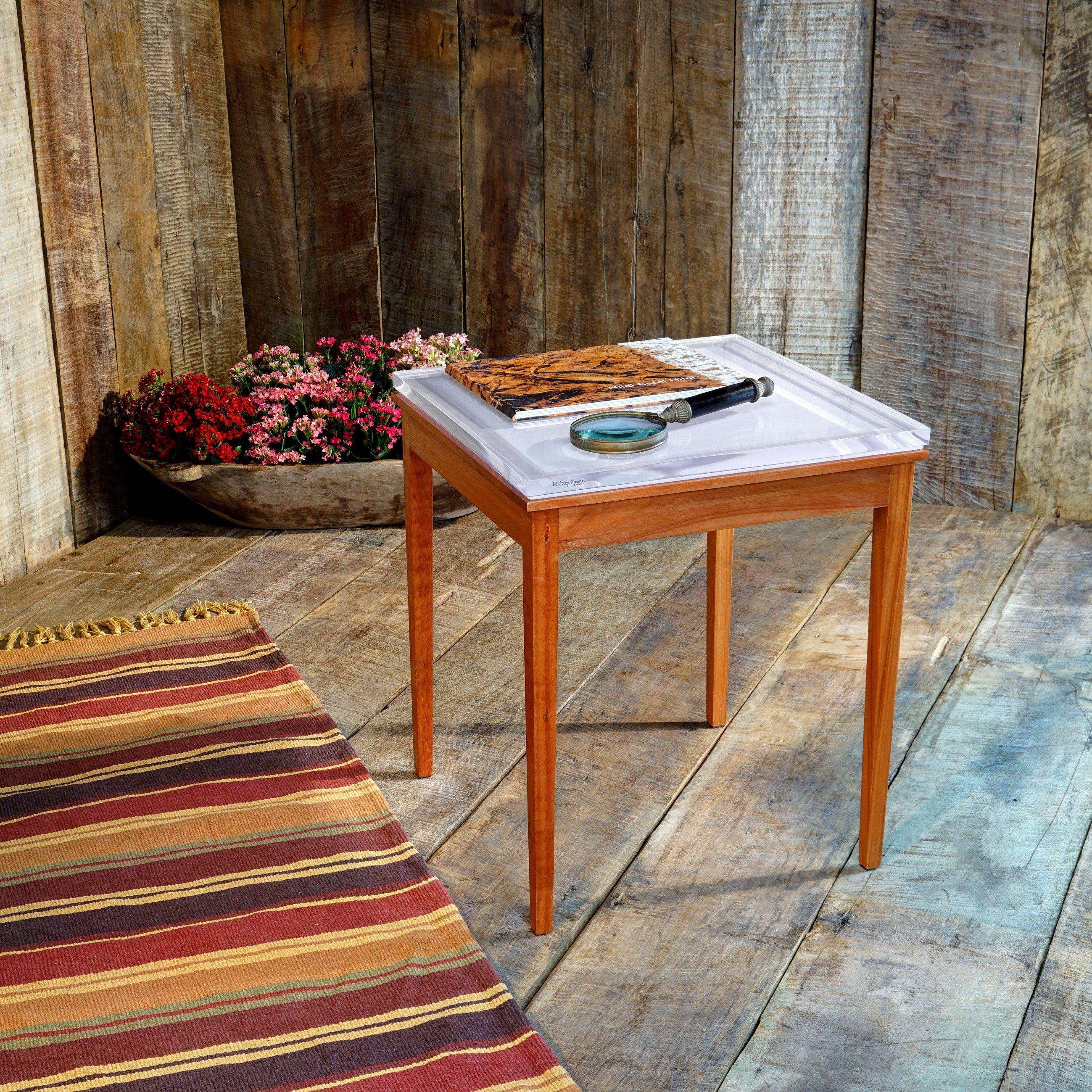 Mesa de Canto (1 tampos) fabricada em resina de poliéster. Passa por um processo de acabamento artesanal que garante a máxima qualidade e durabilidade. A madeira utilizada é de plantios sustentáveis, da marca LYPTUS. Ela recebe um selador e um verniz protetor sem brilho. Isso dá a ela uma proteção à respingos d'água, mas não a torna à prova d'água.