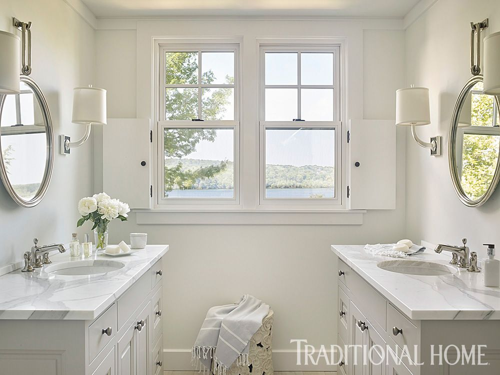 Guest Bath Twin vanities alllow two guests to clean up simultaneously.  Simple wood shutters fold back to permit sunshine and lake views.
