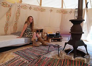tee pee interiors | There are rugs on the wooden floor, low tables and mattresses, etc ...