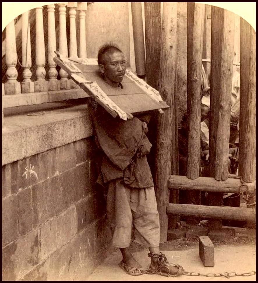 """Person in a portable stock or """"cangue"""" in China."""
