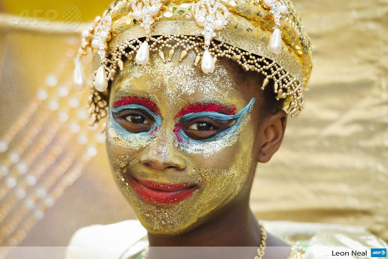 UNITED KINGDOM, London: A girl smiles as she prepares to take part in the parade on the first day of the Notting Hill Carnival in west London on August 25, 2013. Running over two days, the Caribbean carnival puts on a Kids day on the Sunday when costume prizes are awarded and a main parade day on the Monday. AFP PHOTO/LEON NEAL