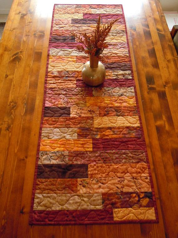 Quilted Autumn Batik Table Runner/Fall Colors Table Runner/Autumn Table Decor/Rustic Warm Colors Table Runner #autumncolors Gorgeous autumn colors in this table runner! All of the top fabrics are batiks in red, gold, orange, and brown. I sewed this in a patchwork style. It looks rustic as well as modern.   It measures 44 x 15. To clean, vacuum or brush. If soiled, wash in cold water on gentle cycle. I like to tumble dry #fallcolors