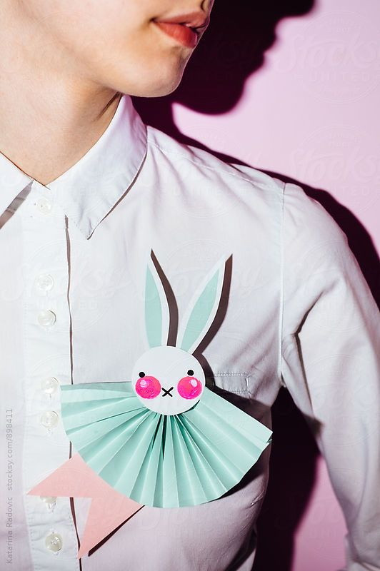 Woman wearing blue Easter bunny rosette made of paper.