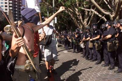 Demonstrators shout as police officers stand guard