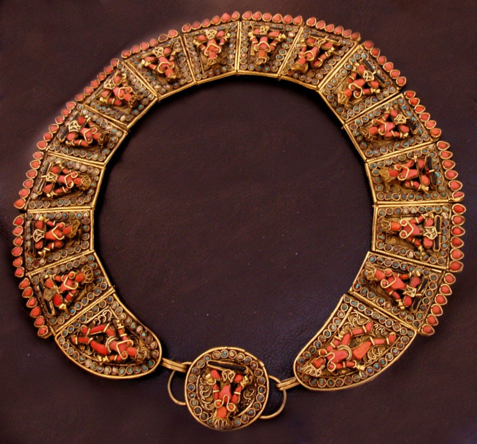 Tibet | Vintage necklace consisting of 16 brass panels, each depicting a standing or sitting 3 dimensional figure, using turquoise and red and black coral stones | ca. 1930s.