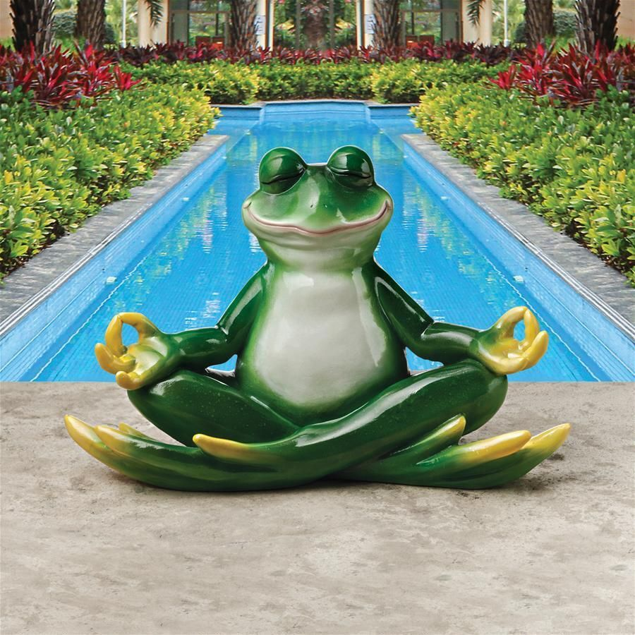A peaceful smile on his face, this yoga frog sits silently, deep in ...