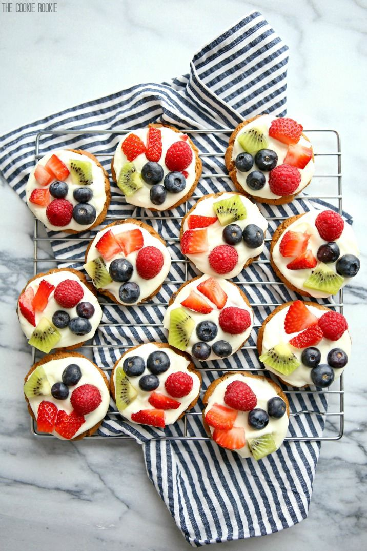 Mini Chocolate Chip Cookie Fruit Pizzas! Such a fun Spring Dessert! Chocolate Chip Cookie base topped with White Chocolate Cream Frosting and mixed fruit!
