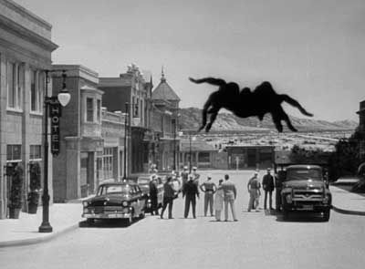 """Tarantula is a B movie from 1954 that was advertised with the tag line, """"More terrifying than any horror known to man comes a creeping crawling monster whose towering fury no one can escape!""""  The movie is about a spider that escapes from an isolated desert laboratory experimenting in giantism and grows to tremendous size as it wreaks havoc on the local inhabitants."""