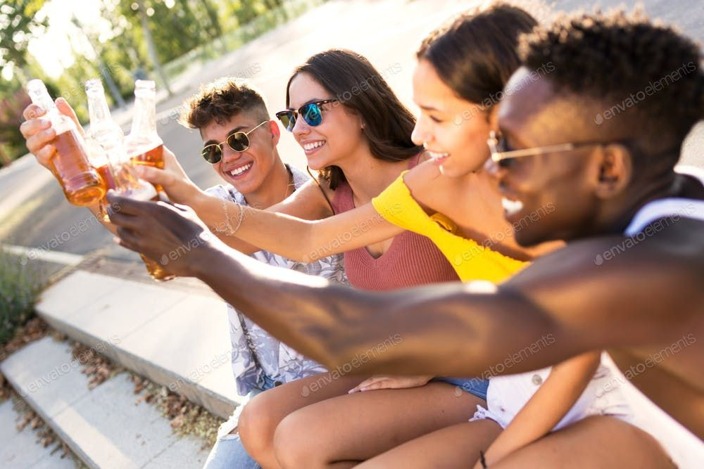 Group of young people toasting with beer in an urban area By nenetuss photos