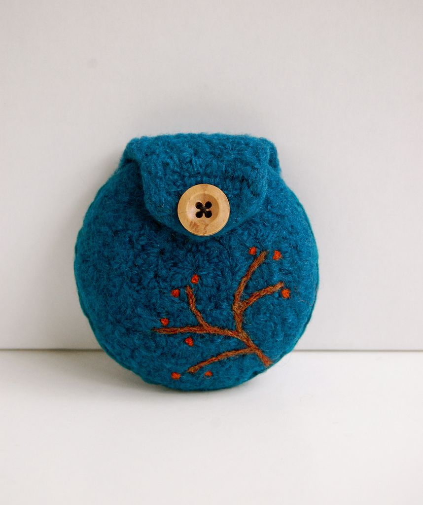Made from 100% teal wool, this change purse was hand crocheted, then wet felted to give the material a more structured texture. A little branch with orange berries was needle felted by hand on the corner of the purse.