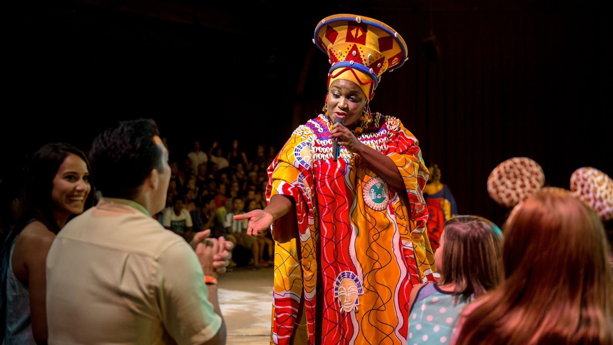 A performer dressed in an African tribal costume reaches