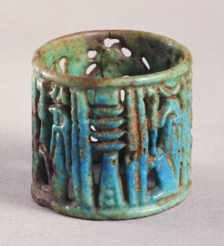 An ancient Egyptian faience openwork ring adorned with a djed pillar, symbol of the underworld god Osiris and stability. Princeton University Art Museum
