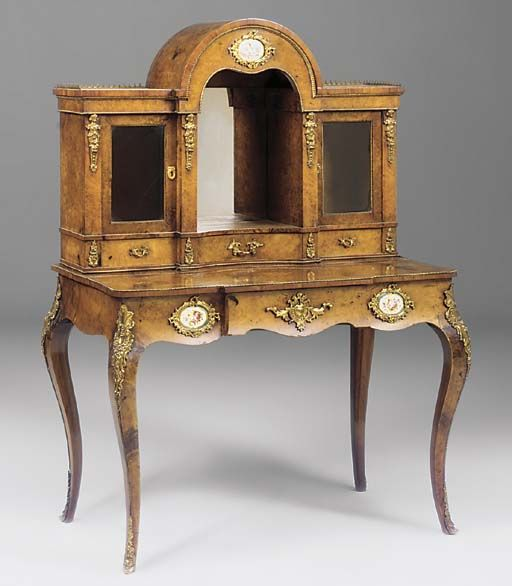 A VICTORIAN GILT METAL MOUNTED BURR WALNUT DISPLAY WRITING TABLE Mounted with three oval porcelain plaques. Christie's.