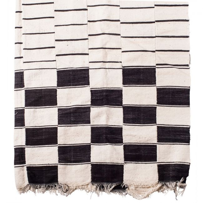 This Khasa style blanket is made by the Fulani weavers from the Niger Bend of Mali and Niger. Woven of white sheep's wool on a horizontal strip loom, they are made up of four to six panels and sewn together.