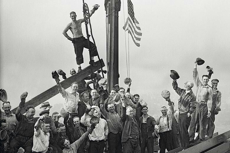 Construction workers raise the american flag at the