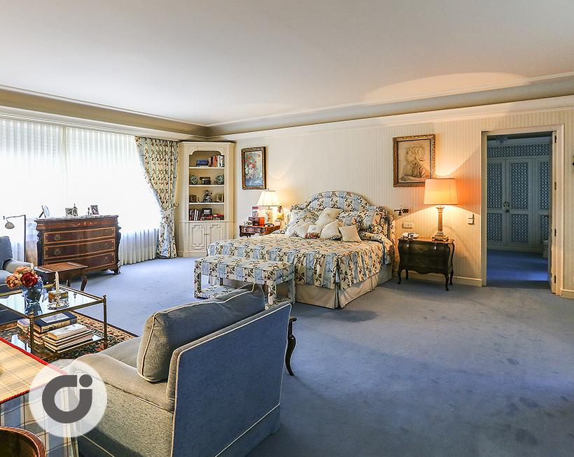 Uno de los nueve dormitorios de este chalet, decorado en tonos ...