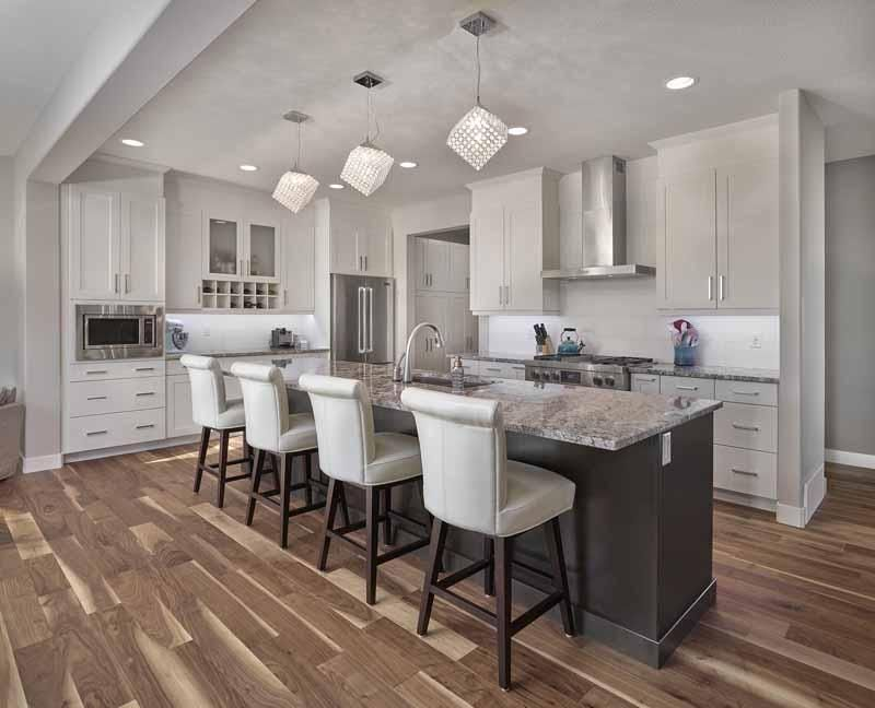 White Kitchen with extra-long island in contrasting colour, crystal pendants #buildwithkimberley #yegre #customhomes