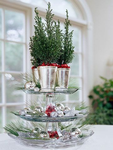 Tiered Ornament Platter - Raid your kitchen for a tiered serving platter. Fill the bottom tiers with silver ornaments and evergreen sprigs. Top the decoration with three small evergreen trees in silver pots. Dot the platter with cranberries for bursts of color.