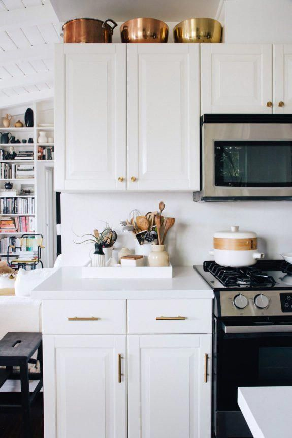 copper and brass cookware above white cabinets with ...