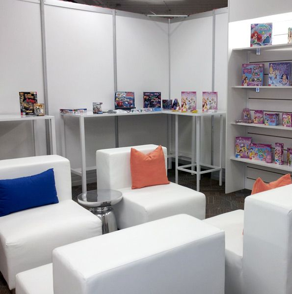 Trade show shelving, Colette communal tables, and Luxor modular seating with accent pillows.