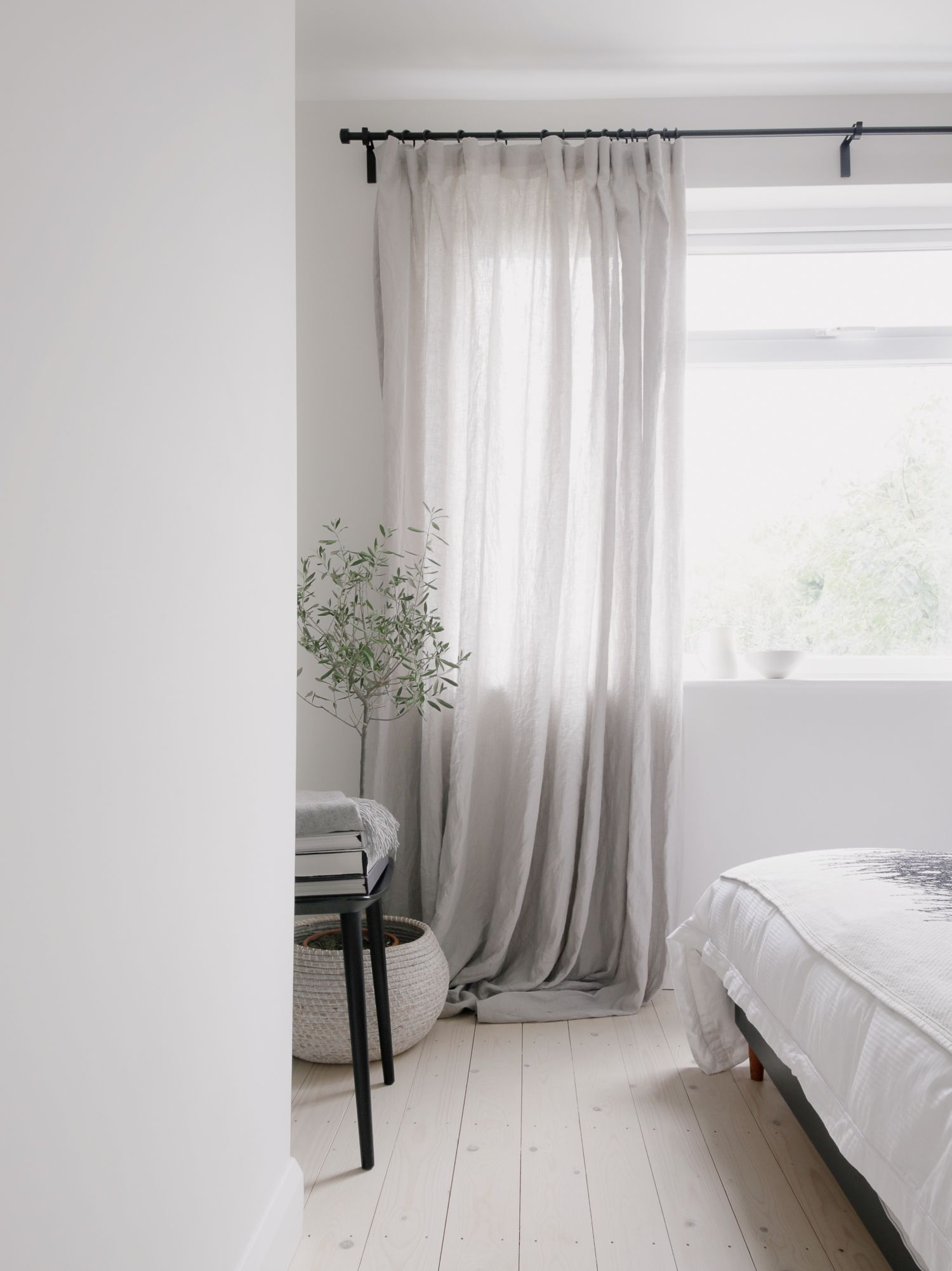 LIght minimalist bedroom with pale wooden flooring and linen curtains.