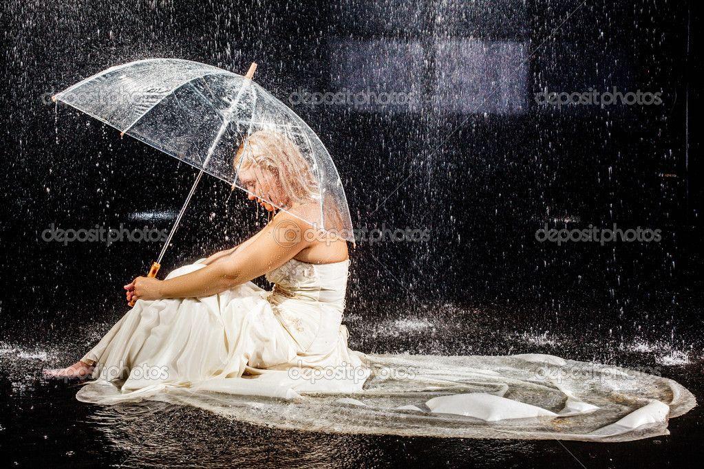 Novia sentado bajo la lluvia con paraguas transparente