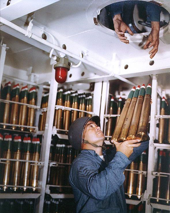 Gunner's Mate First Class Carrick N. Thomas passed a clip of four 40mm rounds through a hatch in a 40mm handling room of Battleship USS Alaska, off Iwo Jima, 6 Mar 1945. (US National Archives)