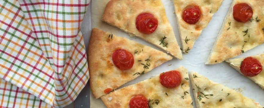 Una base di focaccia arricchita con pomodorini ciliegia, timo fresco e olio doliva extravergine.