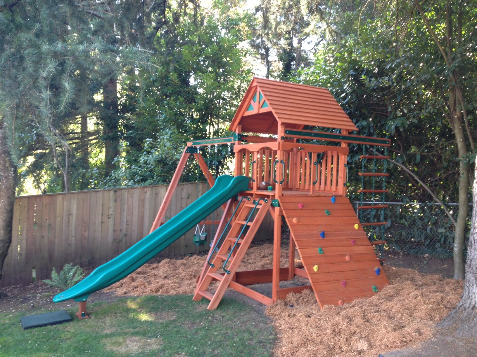 play structure with swings slide and rock wall all the