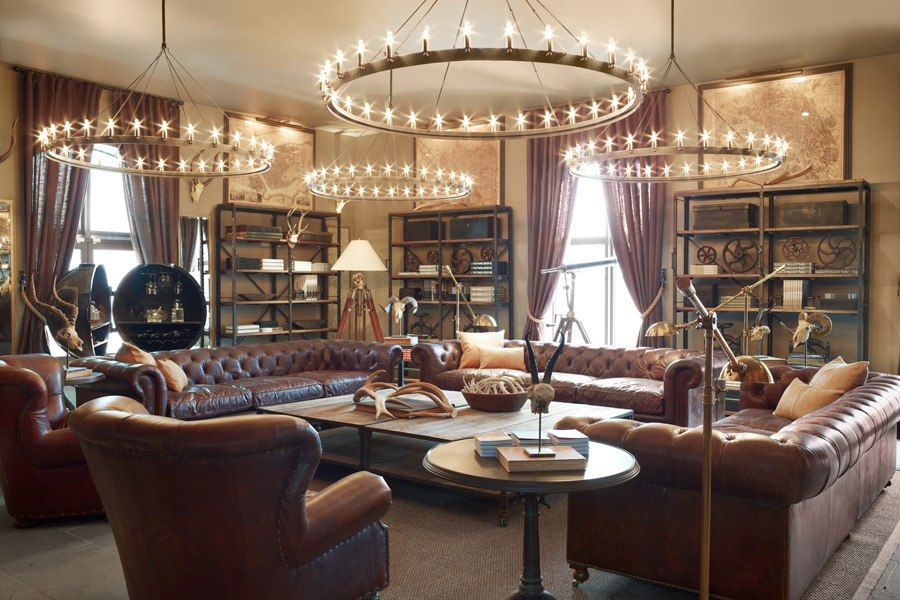 Rh Rebranding Camino Chandeliers Illuminate A Seating Area Furnished With Kensington Leather Sofas