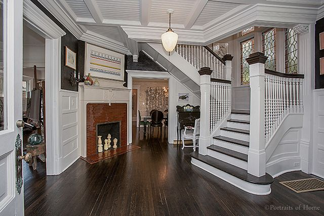 Historical Queen Anne house in Glen Ellyn IL for sale has original coal  fireplace and this stunning staircase. Beautiful windows and lighting and  the turret