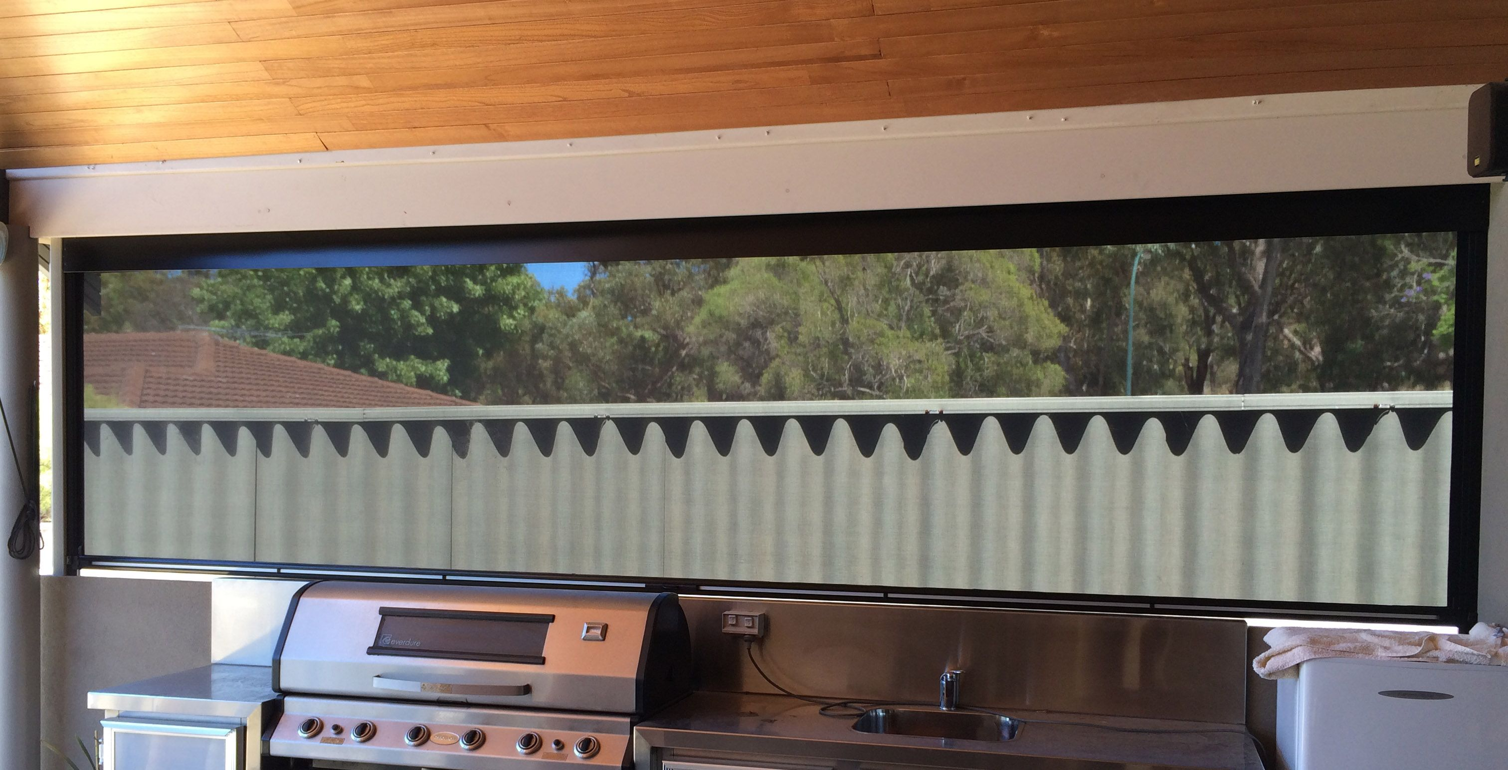 Roller blind covering an outdoor BBQ patio area. | Outdoor Blinds ...