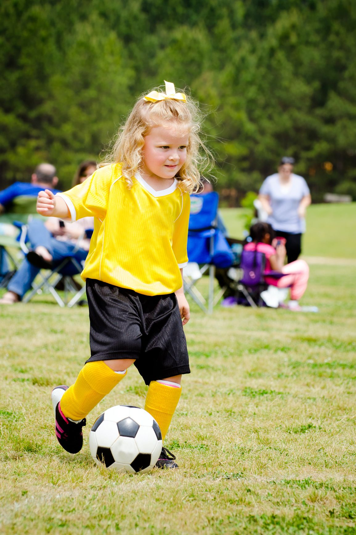 Cute young girl in uniform playing in organized youth