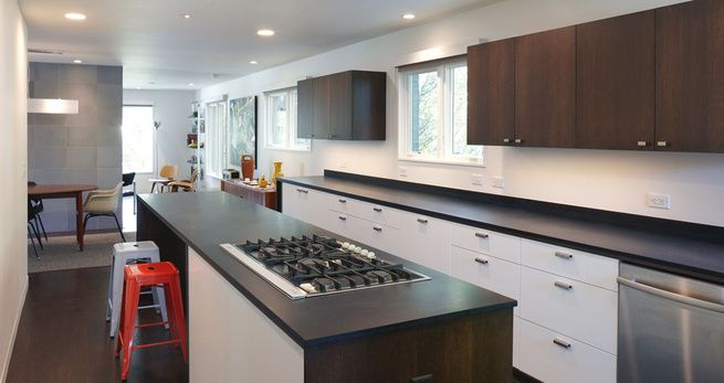 Really clean kitchen. Dark wood. White walls. Stainless steel. Built in stove.