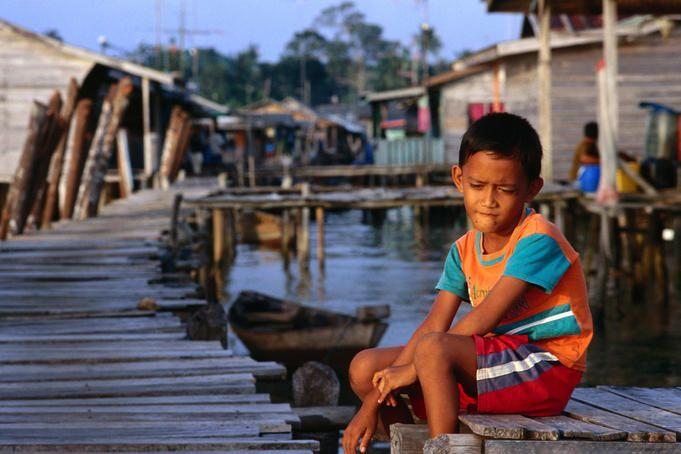 Sumatra, Kampung Bugis: Boy sitting on a pier in Kampung Bugis.