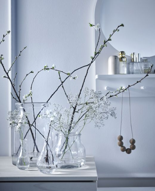 on a side table branches and flowers sit in glass vases. Black Bedroom Furniture Sets. Home Design Ideas